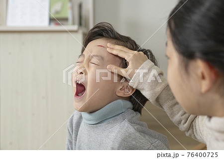 Asian little sister looking over at wounded brother 76400725