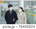 Asian couple with face masks in train station 76400924