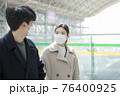 Asian couple with face masks in train station 76400925