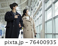Asian couple with face masks in train station 76400935