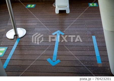 床に貼られたブルーのソーシャルディスタンス表示のテープ 76423201