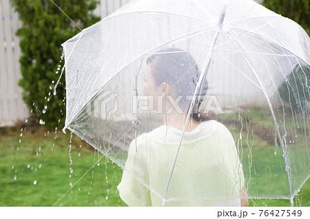 傘をさす女性 76427549