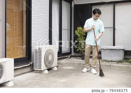 掃き掃除をするハウスクリーニング の男性 76436375