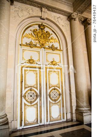 フランスパリのベルサイユ宮殿の中にある金色の飾りのついた大きなアーチ形のドア 76449437