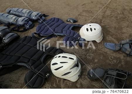土のグランドに並べられたキャッチャーのプロテクターなどの野球道具 76470622