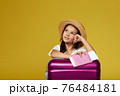 child with pink suitcase on yellow background. 76484181