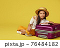 little girl with suitcase and passport sitting on floor 76484182