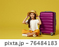 little girl with suitcase and passport sitting on floor 76484183