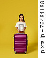 Happy little child girl in hat with pink suitcase 76484188