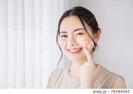 歯を指差す若い女性 76489092