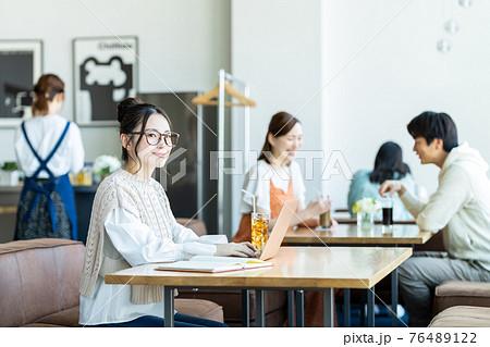 カフェでテレワークする若い女性 76489122