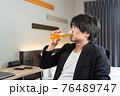ビジネスホテルでビールを飲んでくつろぐ男性 76489747