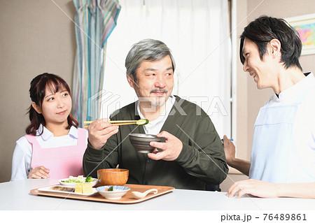 食事をする高齢者男性とエプロン姿の男女の介護士 76489861