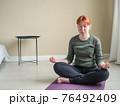 Woman sitting on floor in posture of meditation 76492409