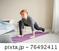 Girl coach doing exercises before laptop. Online 76492411