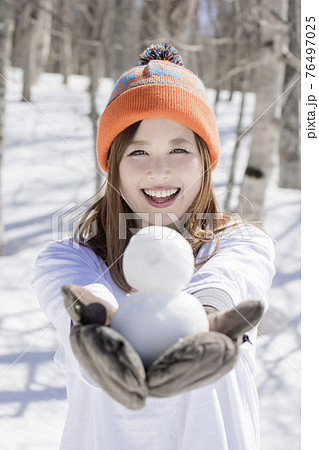 スキー場で小さい雪だるまを作って見せる若い女性 スキースノーボードイメージ  76497025