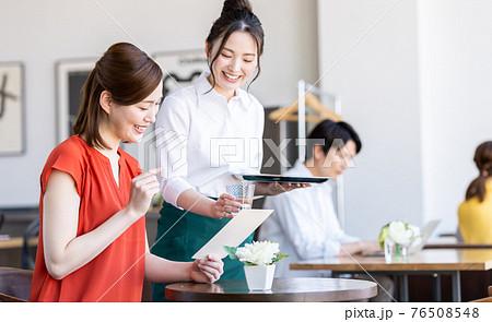 カフェで注文する若い女性と接客するスタッフ 76508548