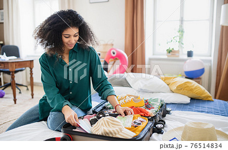 Young woman with suitcase packing for holiday at home, coronavirus concept. 76514834