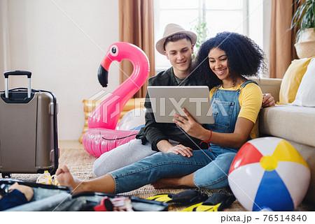 Young couple with tablet packing for holiday at home. 76514840
