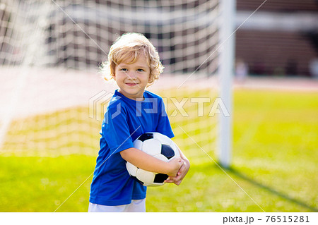 Kids play football. Child at soccer field. 76515281