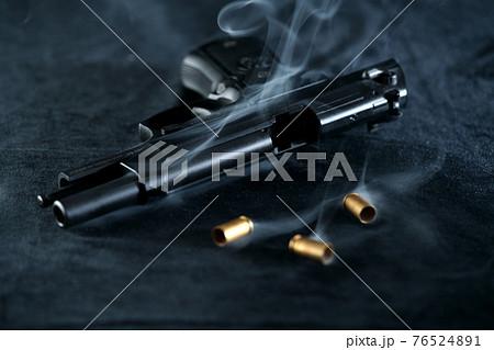 発砲後の拳銃 M92Fミリタリーモデルと薬莢 76524891