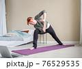 Girl doing yoga asanas near bed looking into 76529535