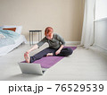 Girl doing stretching at home looking into laptop 76529539