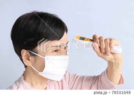 マスクをして非接触型体温計を使う横向きのシニア女性 76531049
