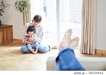 ソファで寛ぐアジア人のお父さんと動画を見る母子 76534442