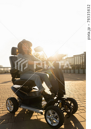 Woman riding an electric scooter  76535632