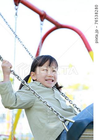 公園のブランコで遊ぶ5歳の女の子 76538280
