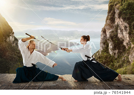 Man and woman, teacher fighting Aikido, training martial arts on meadow in front of lake and mountains 76541944