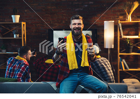 Group of friends watching TV, sport match together. Emotional man cheering for favourite team, celebrating successful betting. Concept of friendship, leisure activity, emotions 76542041