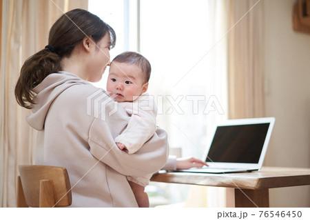 赤ちゃんの子守りをしながら仕事をするアジア人のお母さん 76546450