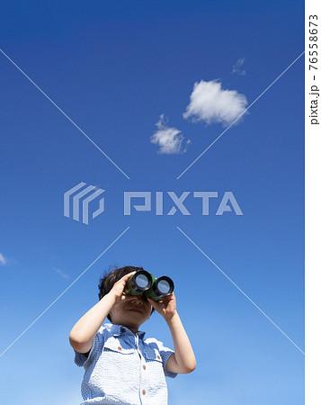 青空のもとで双眼鏡をのぞく少年 76558673