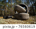 old tire in the forest, pollution of nature car tires 76560619