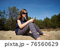 cute little girl holds phone in hand and sits in summer forest 76560629