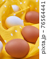 Chicken eggs lying on a soft textile cloth. 76564441