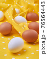 Close-up eggs on yellow textile cloth. 76564443
