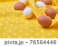 Still life eggs on a yellow wrinkled fabric cloth. 76564446