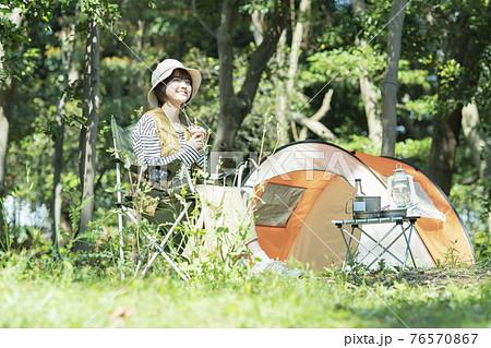 ソロキャンプイメージ・テントの前でくつろぐ若い女性 76570867