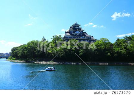 青空の岡山城天守閣 スワンボートの家族連れ 76573570