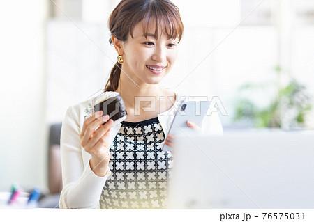 明るい室内でおにぎりを食べる女性 76575031