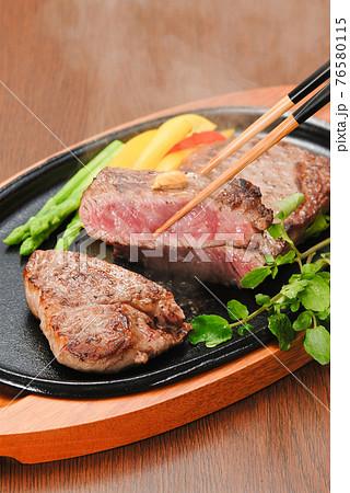 鉄板で焼くステーキを箸で持ち上げ湯気が美味しそう 76580115