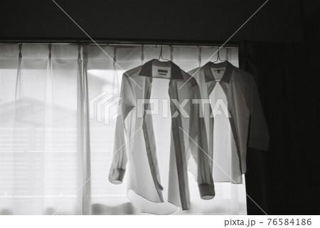 カーテンレールにかかる男女のワイシャツ 76584186