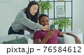 Happy mixed race couple talk laugh looking at smartphone using funny apps sit on couch. Smiling man and woman relaxing at home having fun in social media on cellphone online watching video on phone. 76584612