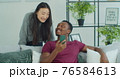 Happy mixed race couple talk laugh looking at smartphone using funny apps sit on couch. Smiling man and woman relaxing at home having fun in social media on cellphone online watching video on phone. 76584613