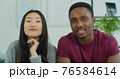 Close up of happy multinational couple sitting on sofa, calling on webcam, video chatting with friends using the phone, waving hand. Young happy family having online video chat webcam while sitting on 76584614