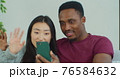 Happy smiling married couple is making video technology call to friends or family with smartphone from home. Man and woman holding smartphone have a funny conversation with friends. 76584632