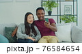 Man and woman making video call, taking selfie sitting on a sofa together at home. Happy multinational couple talking on smartphone making video call at home laughing gesturing enjoying modern 76584654